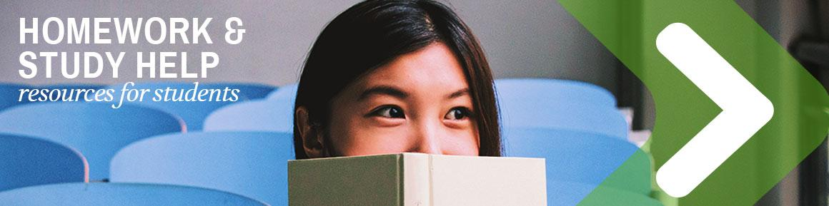 Young Woman Peeking Out from Behind a Book in Classroom Setting